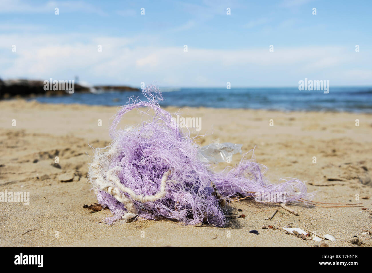 Fishing nylon net on the sand. Garbage on the beach. Dirty sea shore. Environmental pollution. Save the Planet. Ecological problem. Nature theme. - Stock Image