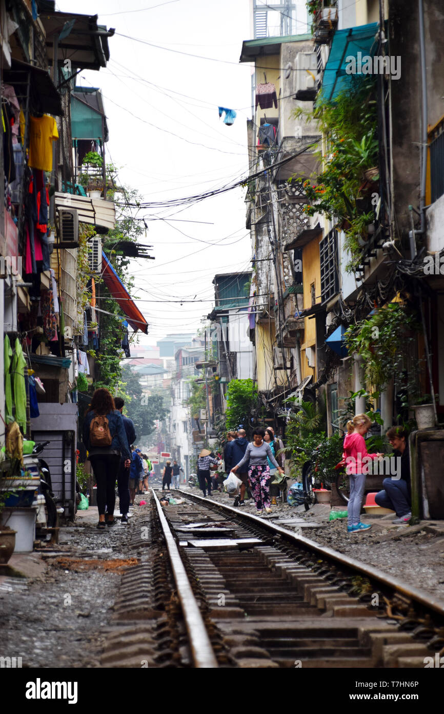 Locals walking around and tourists taking photos of the train street in Hanoi, Vietnam - Stock Image