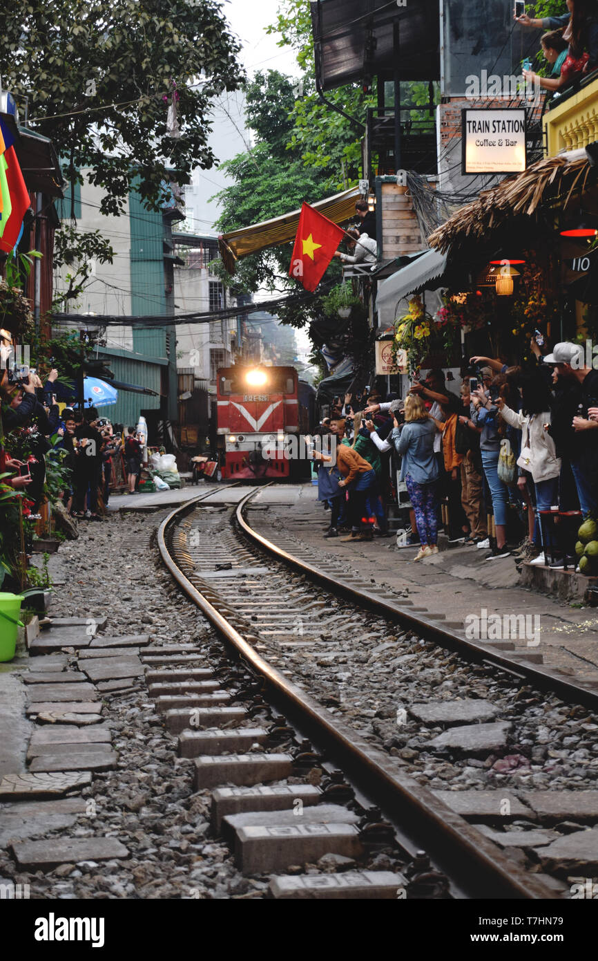 Tourists taking photos of the train running on railway tracks on the narrow train street in Hanoi, Vietnam - Stock Image