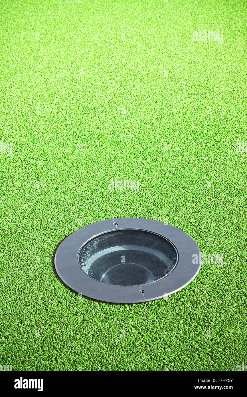 Recessed floor lamp on green gravel floor - image with copy space - Stock Image