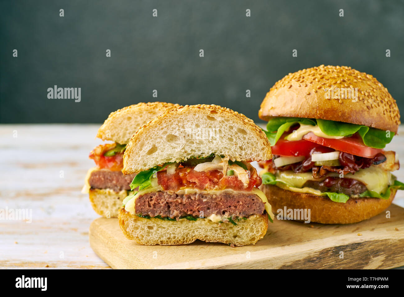 Whole and divided hamburger on old wooden table - Stock Image