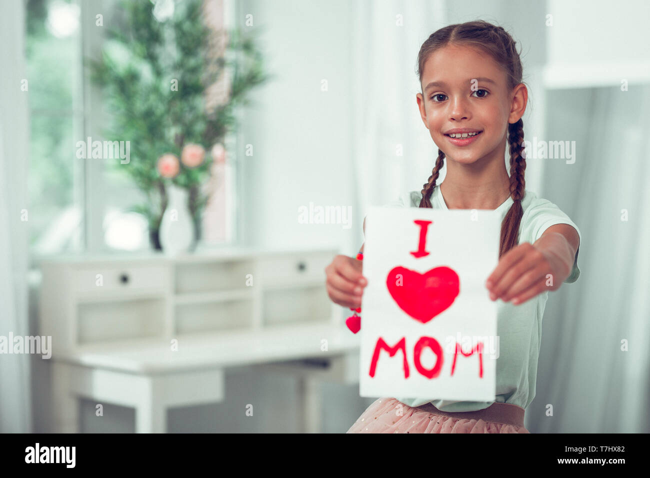 Nice-looking Afro-American girl showing picture with I love mom sign. - Stock Image