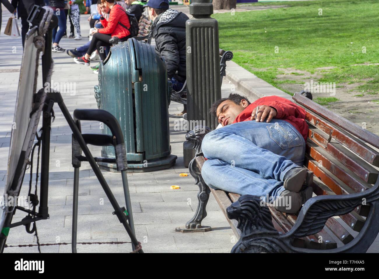 Lviv, Ukraine - 14 April 2019: Homeless man sleeping with cigarette on wooden bench on city street - Stock Image