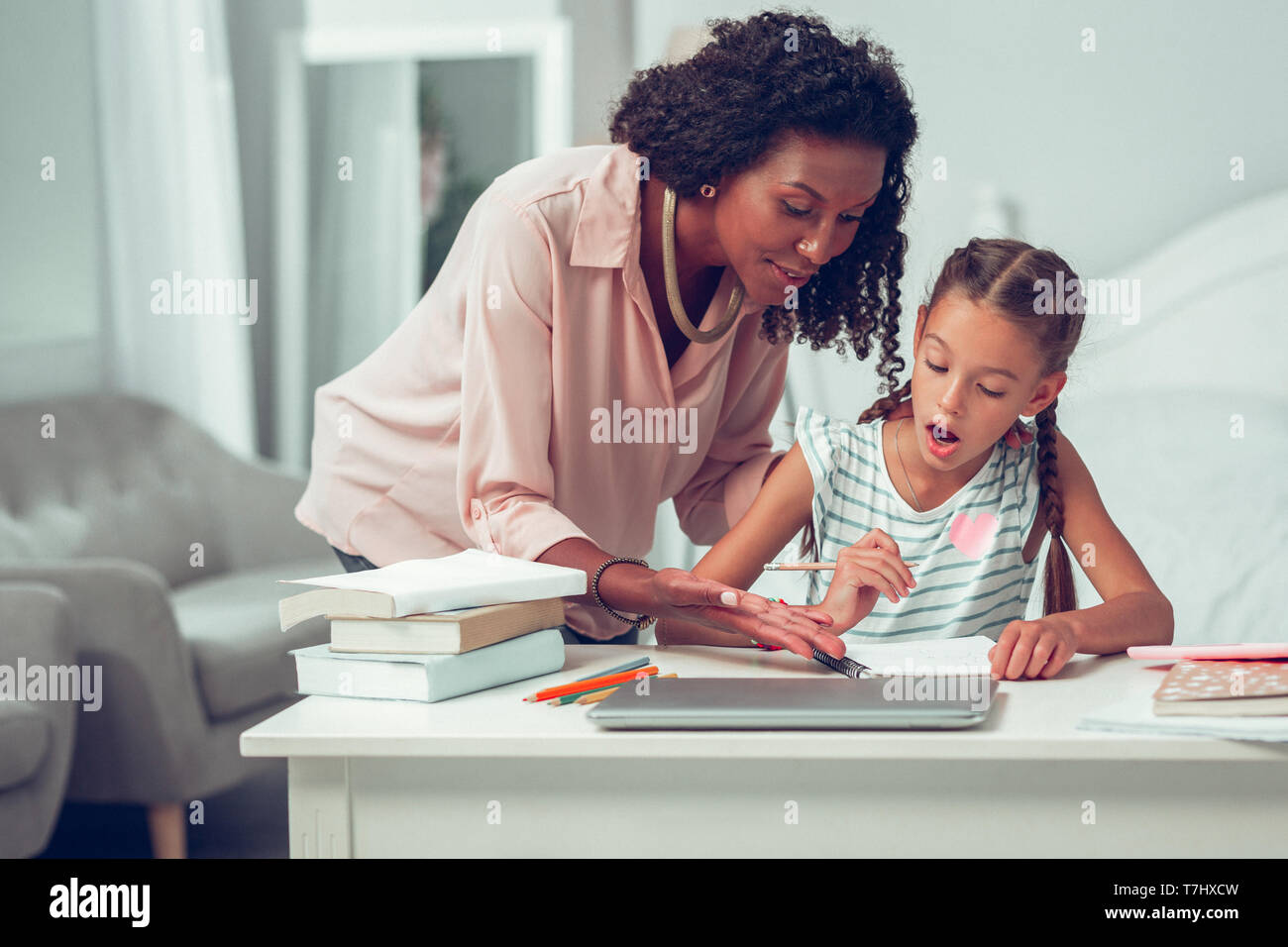 Beautiful curly-haired mother calmly explaining to daughter school homework tasks. - Stock Image