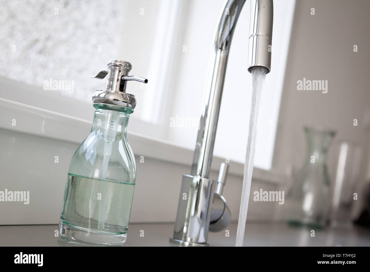 A tap running in the home sink. Also pictured is a bottle of hand wash. - Stock Image