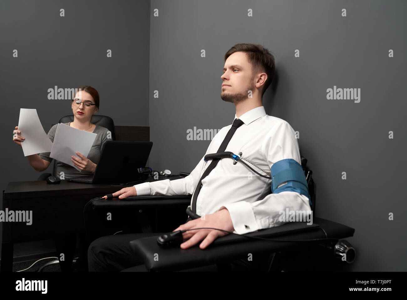 Handsome Man Sitting In Chair In Grey Room And Testing With Polygraph To Hands And Body Attached Sensors Young Woman In Glasses Sitting At Table With Computer Polygraph Looking At Papers Stock