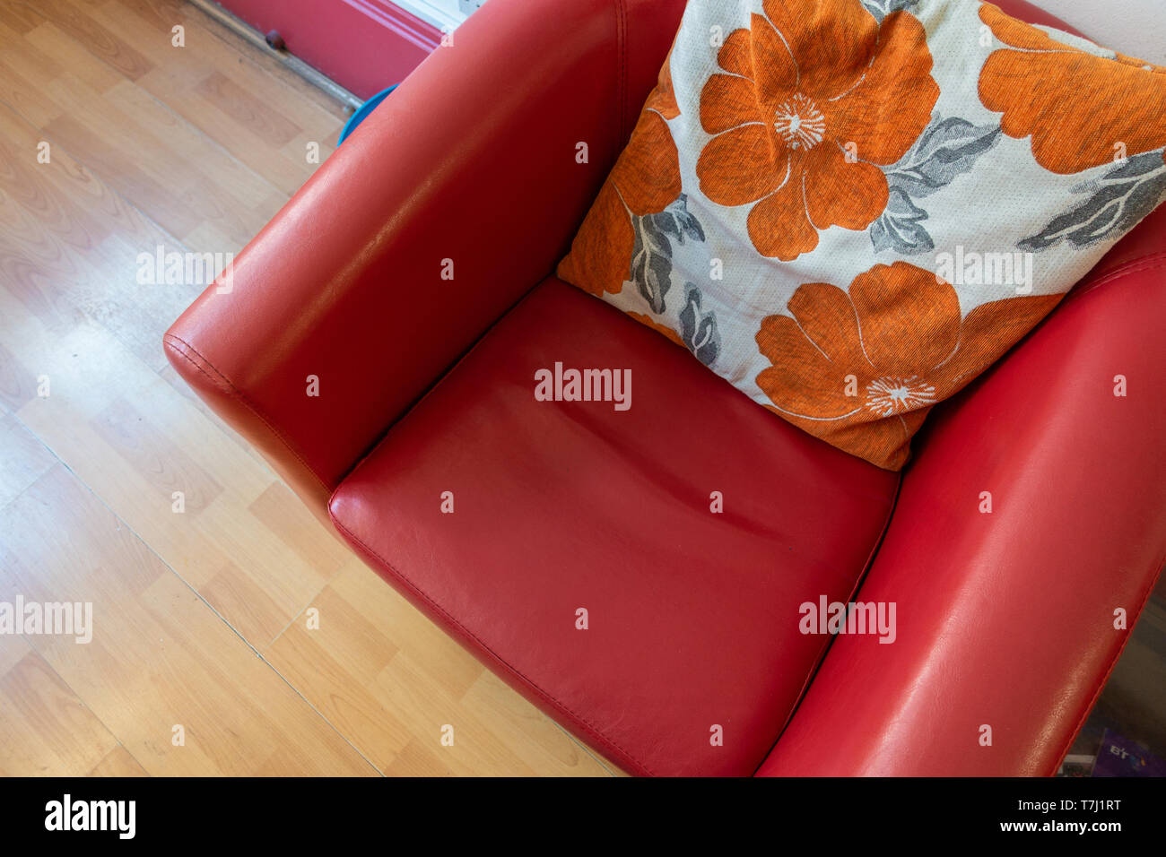 Looking down at a comfortable red armchair with a floral cushion. - Stock Image