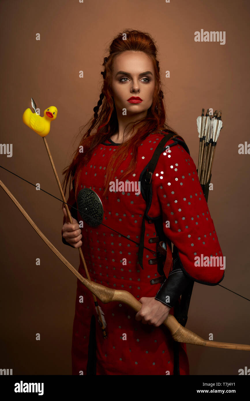 Serious, brave woman, medieval warrior holding bow and arrow with rubber duck. Gorgeous, pretty woman wearing in red tunic looking away, posing in studio. - Stock Image