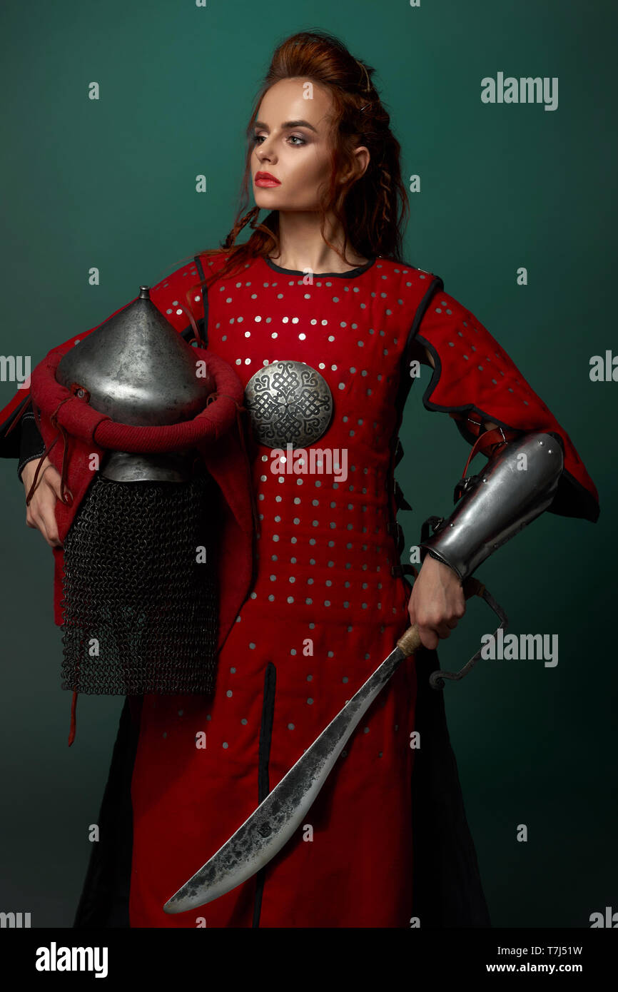 Gorgeous woman warrior holding medieval dagger and helmet, wearing in red medieval tunic. Beautiful woman with red lips and ginger hair posing in studio, looking away. - Stock Image