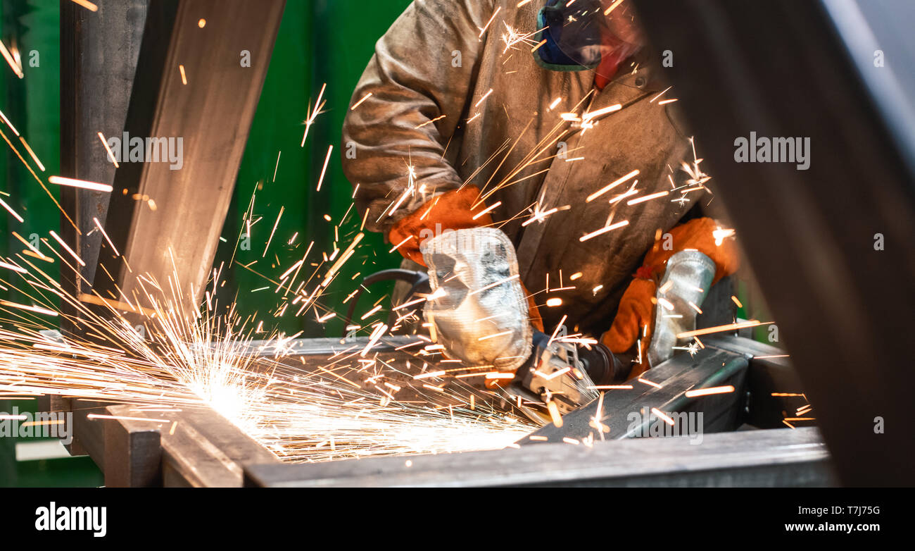 Metalworker working with angle grinder - Stock Image