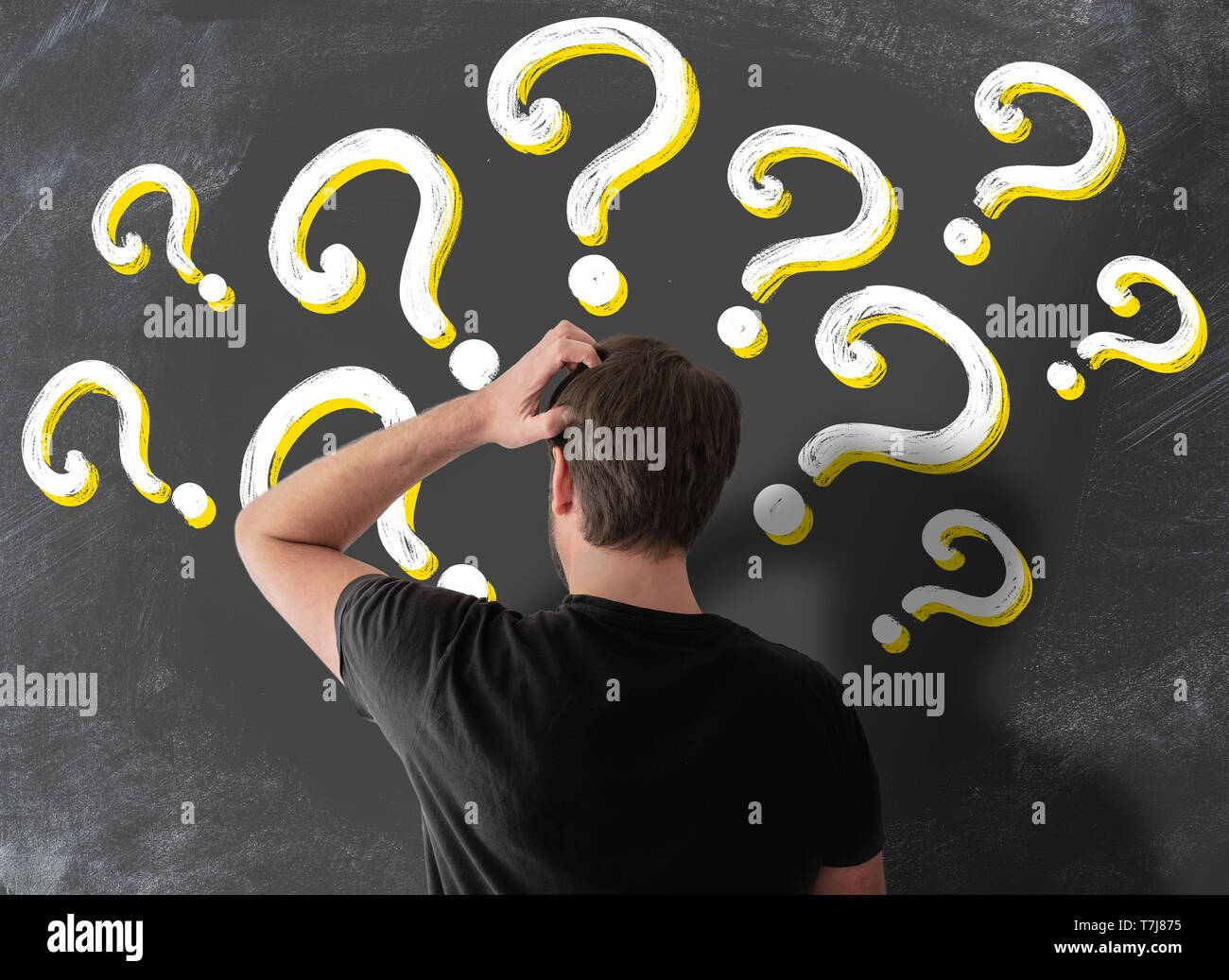 rear view of puzzled man in t-shirt scratching his head in confusion against blackboard filled with question marks - Stock Image
