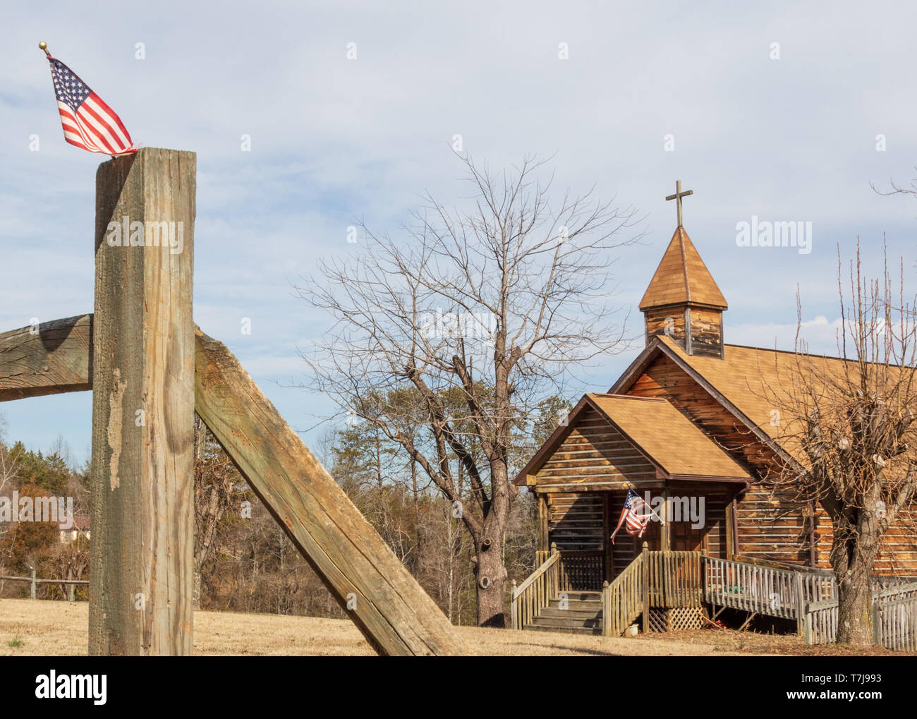 CHESTERFIELD, NC, USA-2/7/15:  Rural log church with rail fence in foreground and American flags. - Stock Image