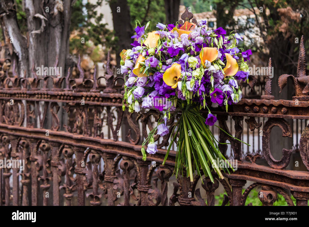 A bouquet of flowers on the wrought openwork fence on the Montjuic Cemetery closeup, Barcelona, Catalonia, Spain - Stock Image