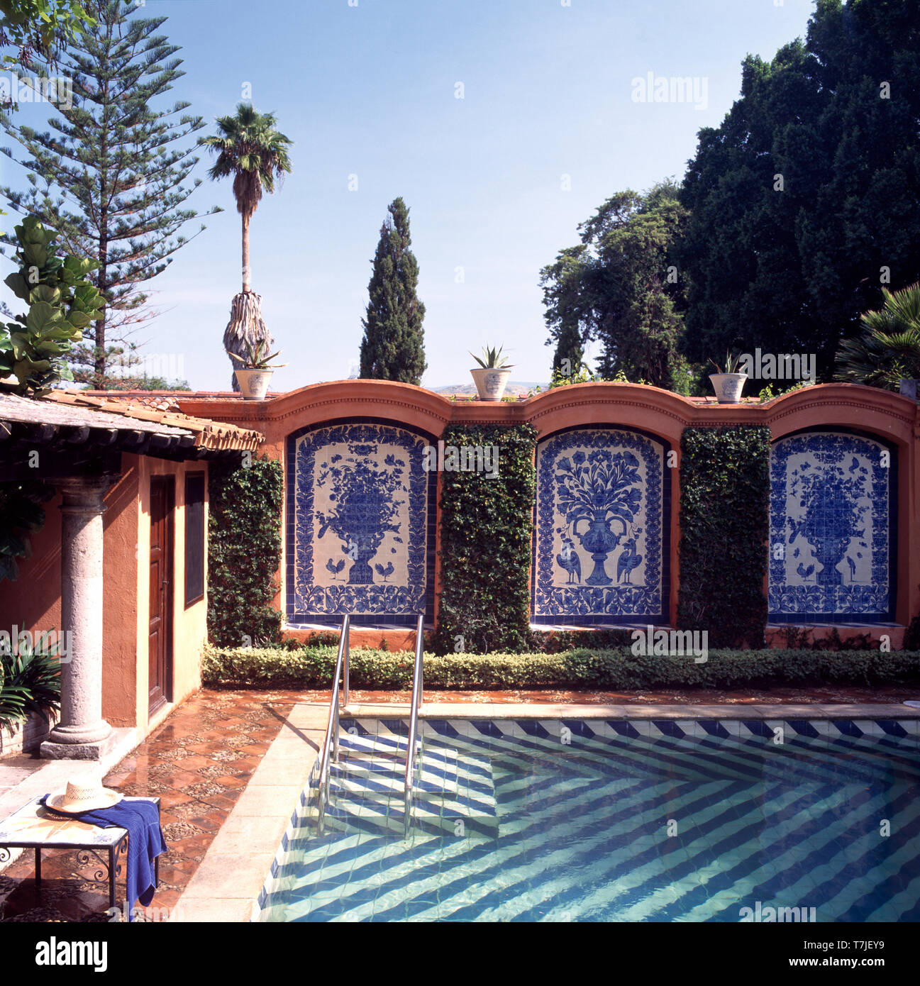 Pictorial tiled walls with clipped ivy surrounding swimming ...