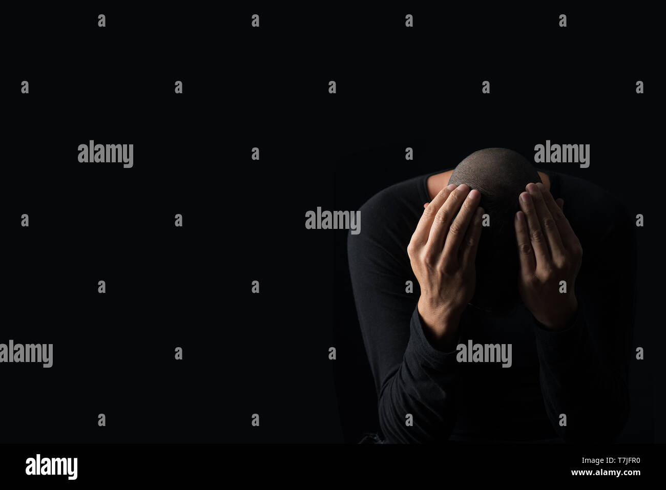 closeup of a desperate young caucasian man with his hands in his head, against a black background, with some blank space on the left - Stock Image