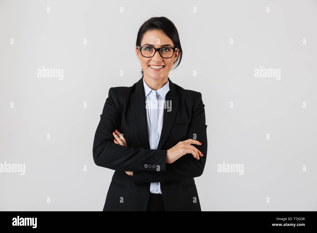 Portrait of successful businesswoman 30s in formal wear and eyeglasses standing in the office isolated over white background - Stock Image