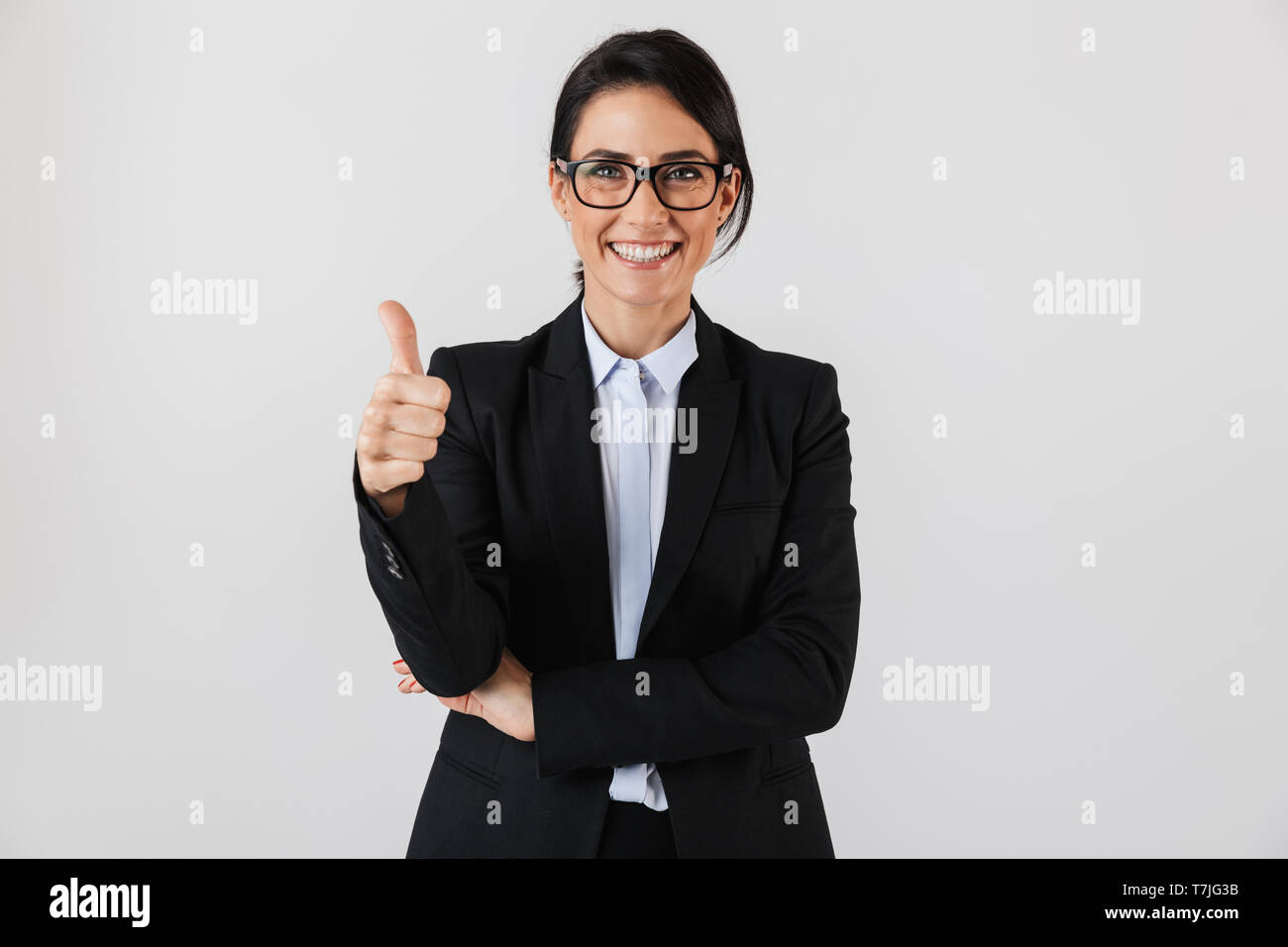 Portrait of caucasian businesswoman 30s in formal wear and eyeglasses standing in the office isolated over white background - Stock Image