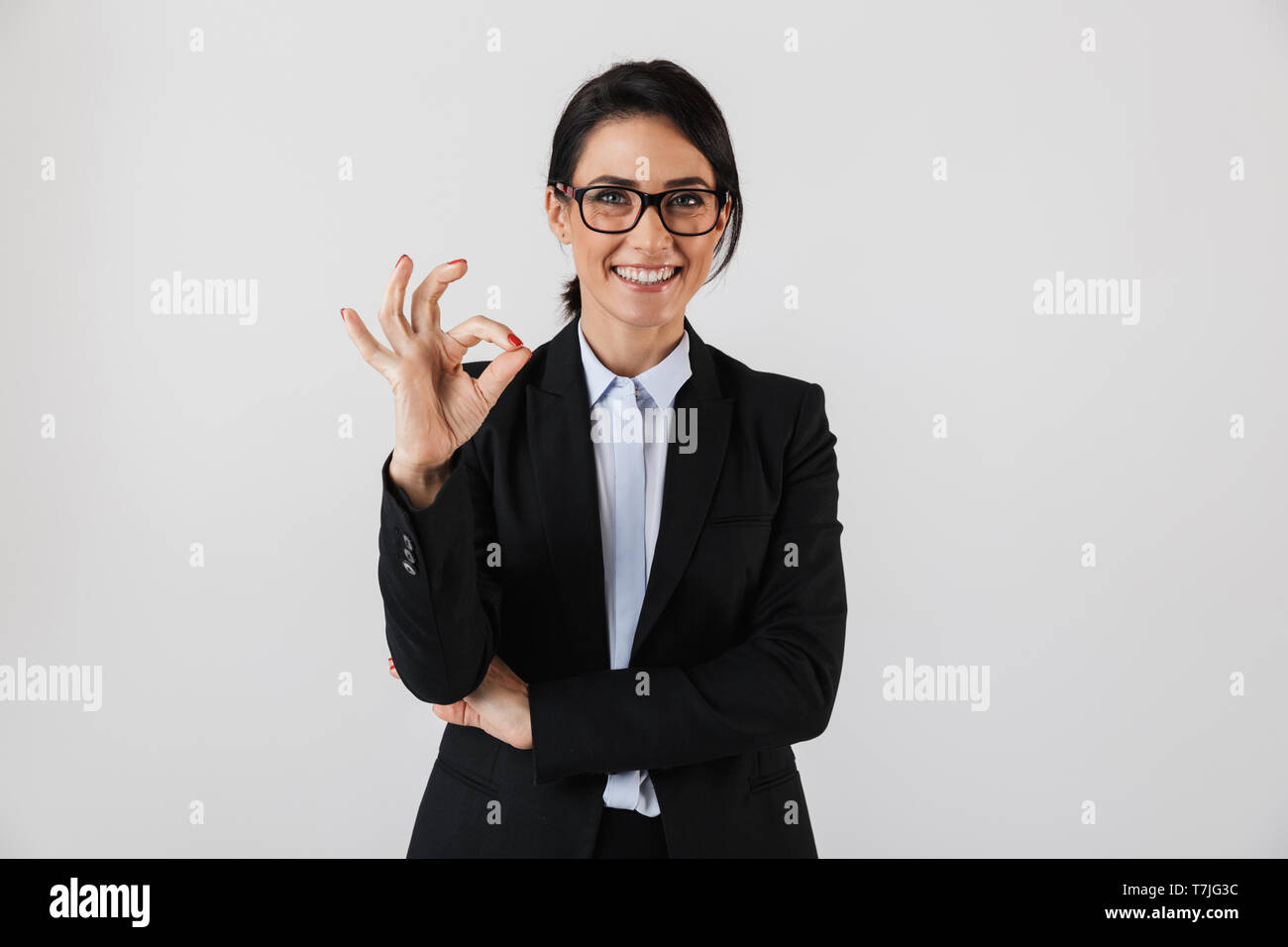 Portrait of attractive businesswoman 30s in formal wear and eyeglasses standing in the office isolated over white background - Stock Image