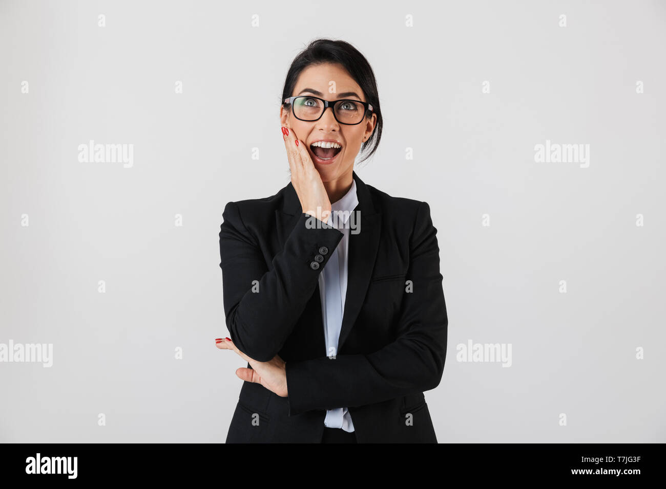 Portrait of happy businesswoman 30s in formal wear and eyeglasses standing in the office isolated over white background - Stock Image