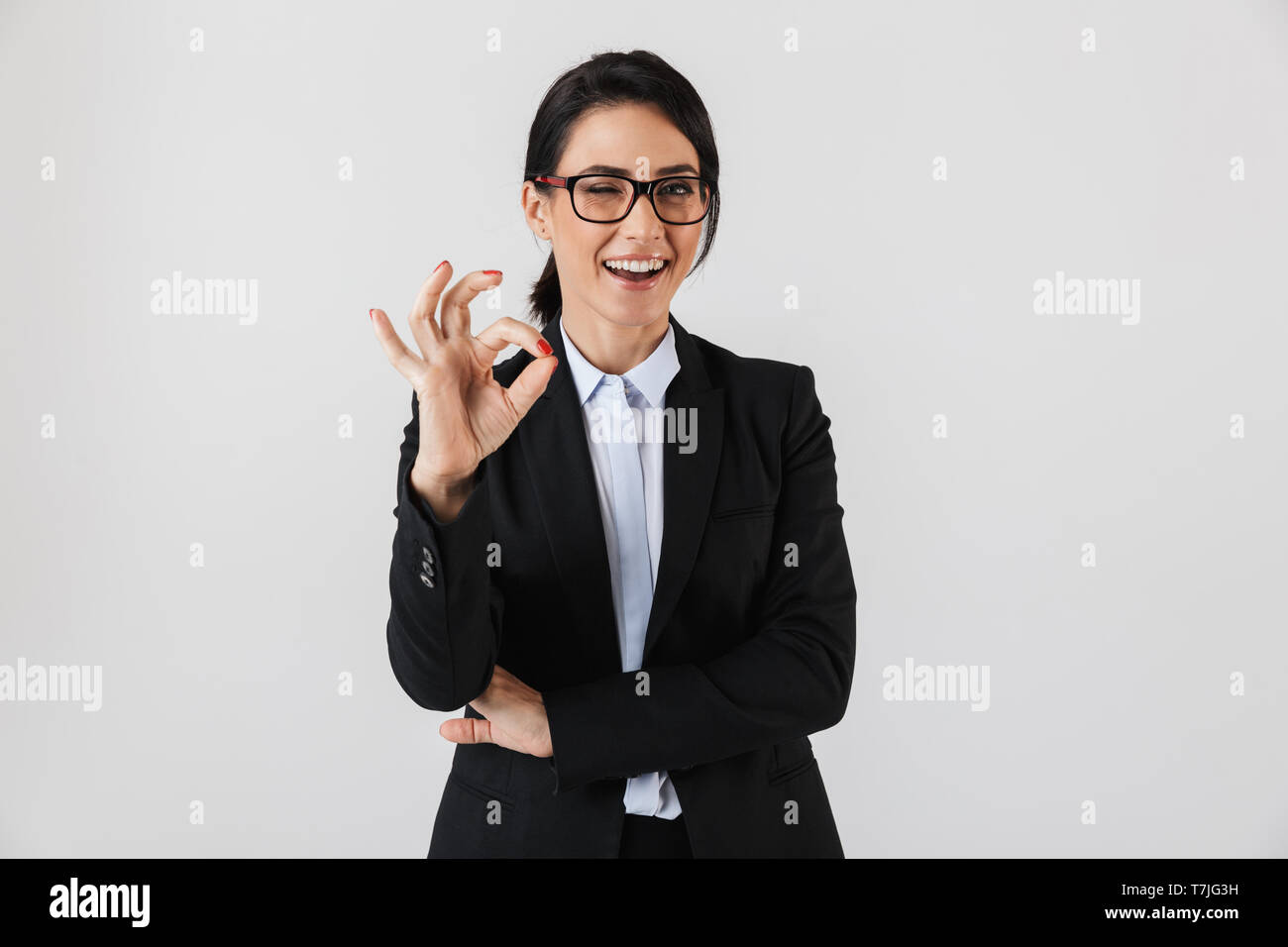 Portrait of adorable businesswoman 30s in formal wear and eyeglasses standing in the office isolated over white background - Stock Image