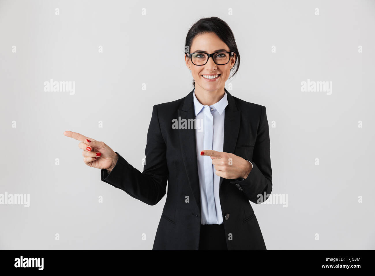 Portrait of european businesswoman 30s in formal wear and eyeglasses pointing fingers aside isolated over white background - Stock Image