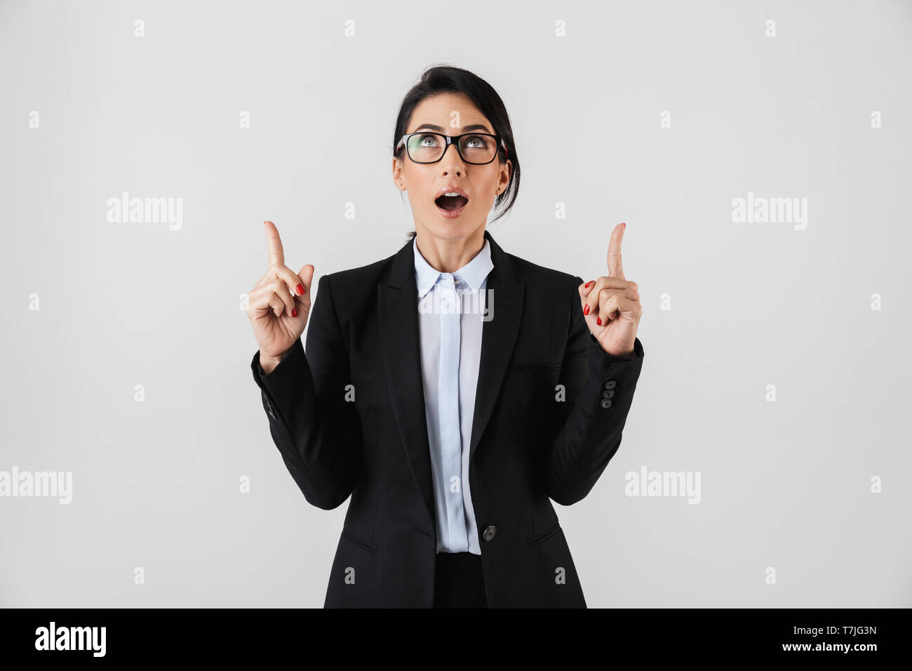 Portrait of cute businesswoman 30s in formal wear and eyeglasses pointing fingers upward isolated over white background - Stock Image