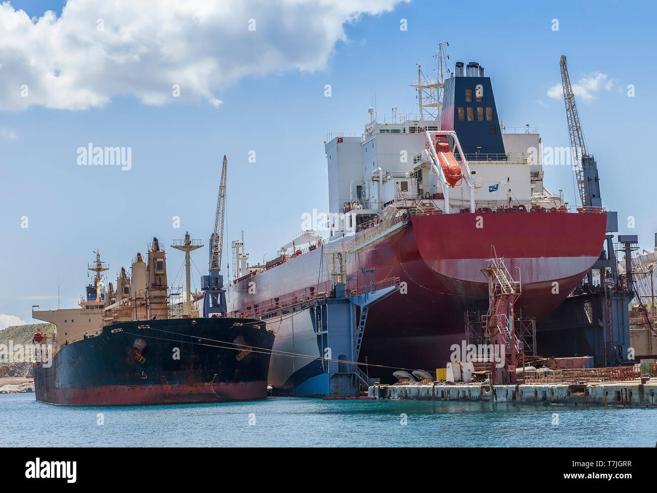 Bulk Carrier On Dry Dock In Shipyard. Heavy lifts cargo ship temporary  laid up next to dry dock. Stock Image. - Stock Image