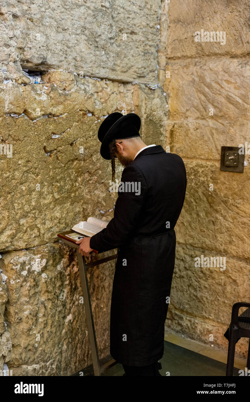 Jewish man prays next to a crack filled with letters containing written prayers at the Western Wall in Jerusalem. Israel Stock Photo
