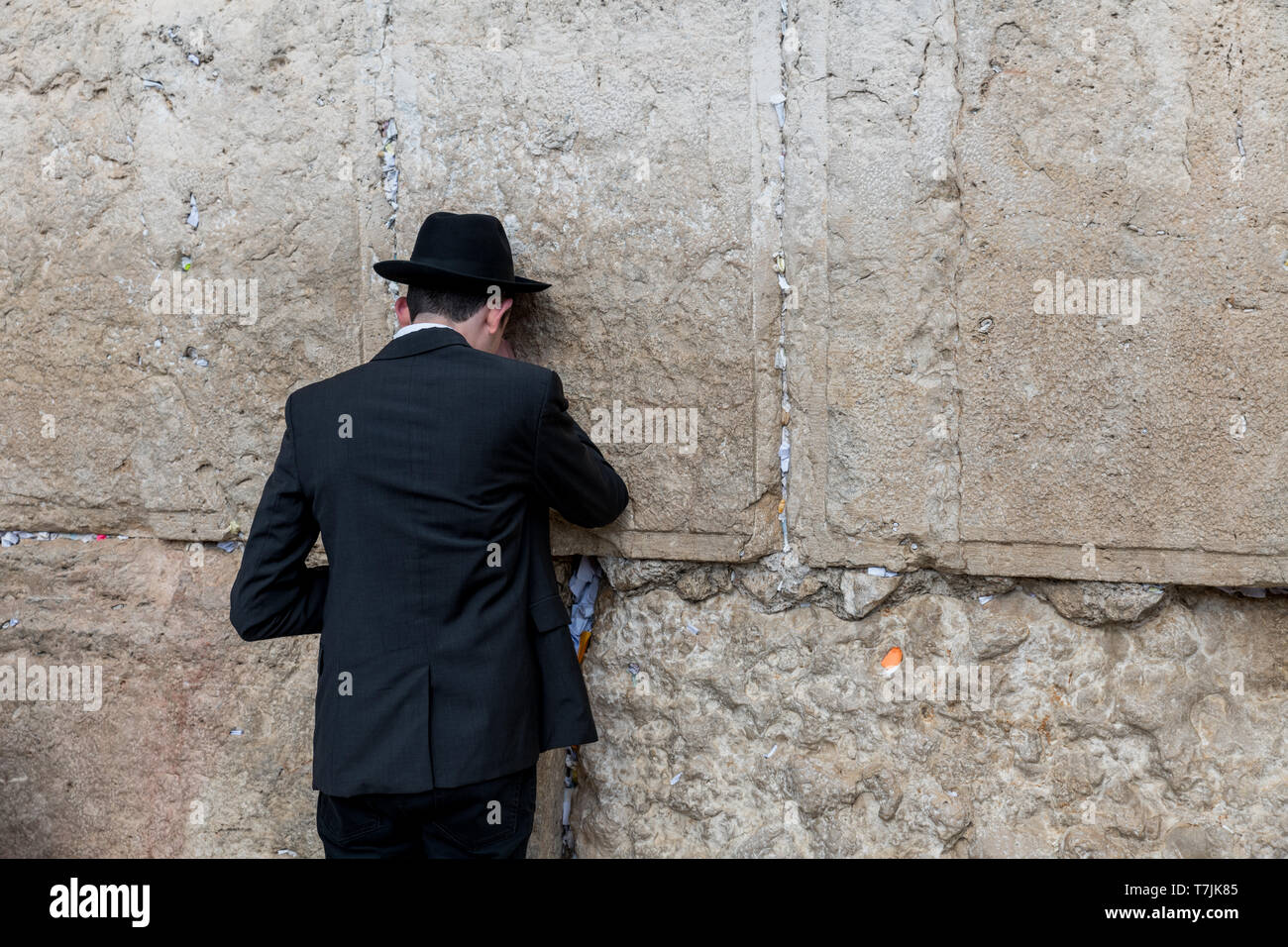 Jerusalem,israel,27-march-2019: Jewish man prays next to a crack filled with letters containing written prayers at the Western Wall in Jerusalem. Isra Stock Photo