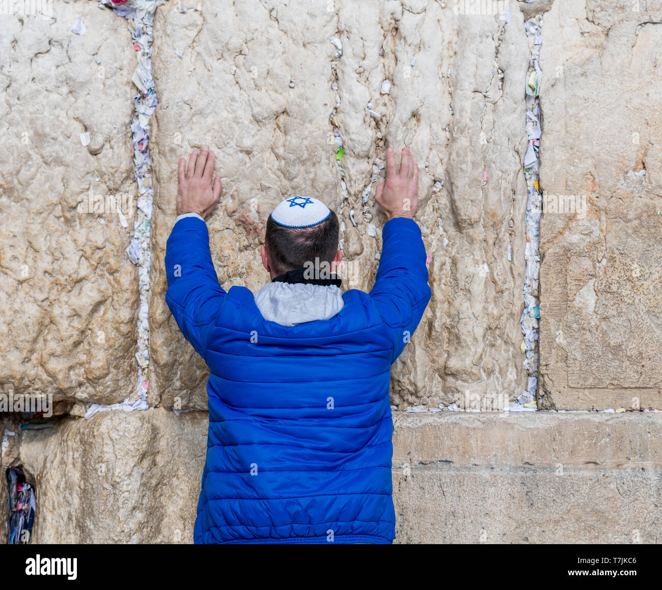 Jerusalem,Israel,27-march-2019:Jewish man prays in blue with keppel with david cross next to a crack filled with letters containing written prayers at Stock Photo