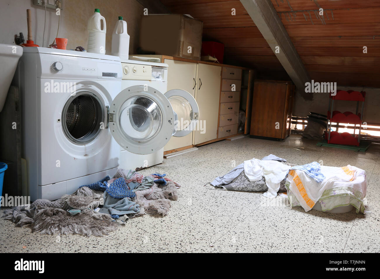 Inside a dusty attic of a school with two big washing machines and tatters dirty - Stock Image