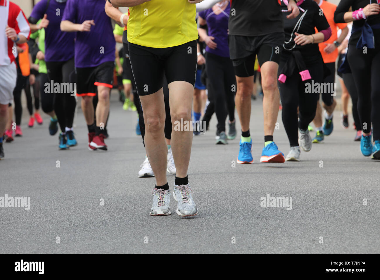 many legs of runners during the race in the city - Stock Image