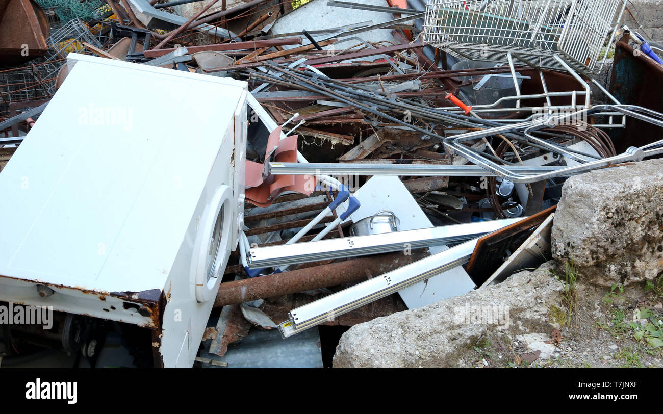 large dump of old and unusable ferrous material and a large broken washing machine - Stock Image