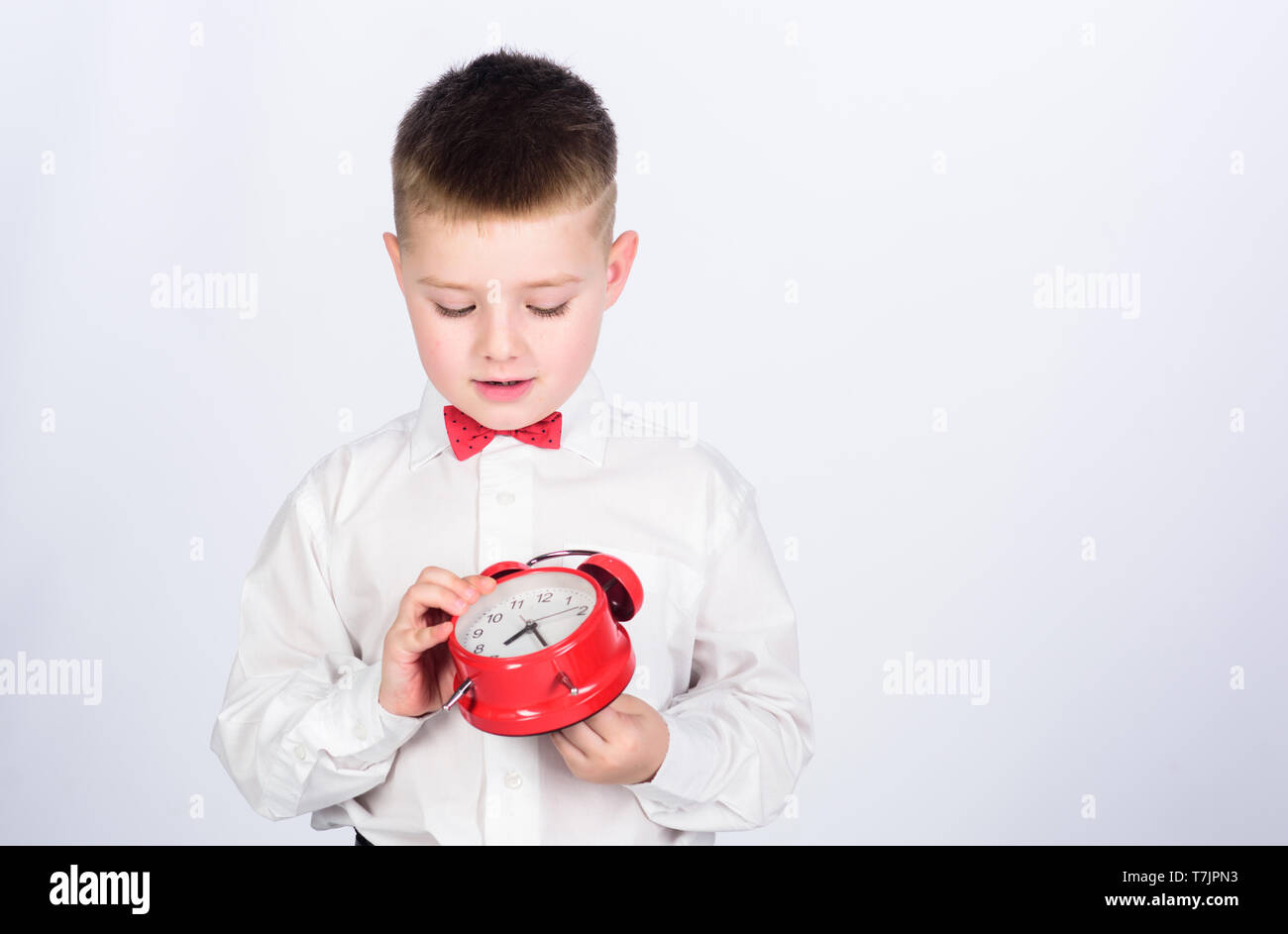 Time management. Morning. little boy with alarm clock. Time to relax. tuxedo kid. Happy childhood. happy child with retro clock in tie. Party time. Businessman. Formal wear. copy space. Billionaire. - Stock Image