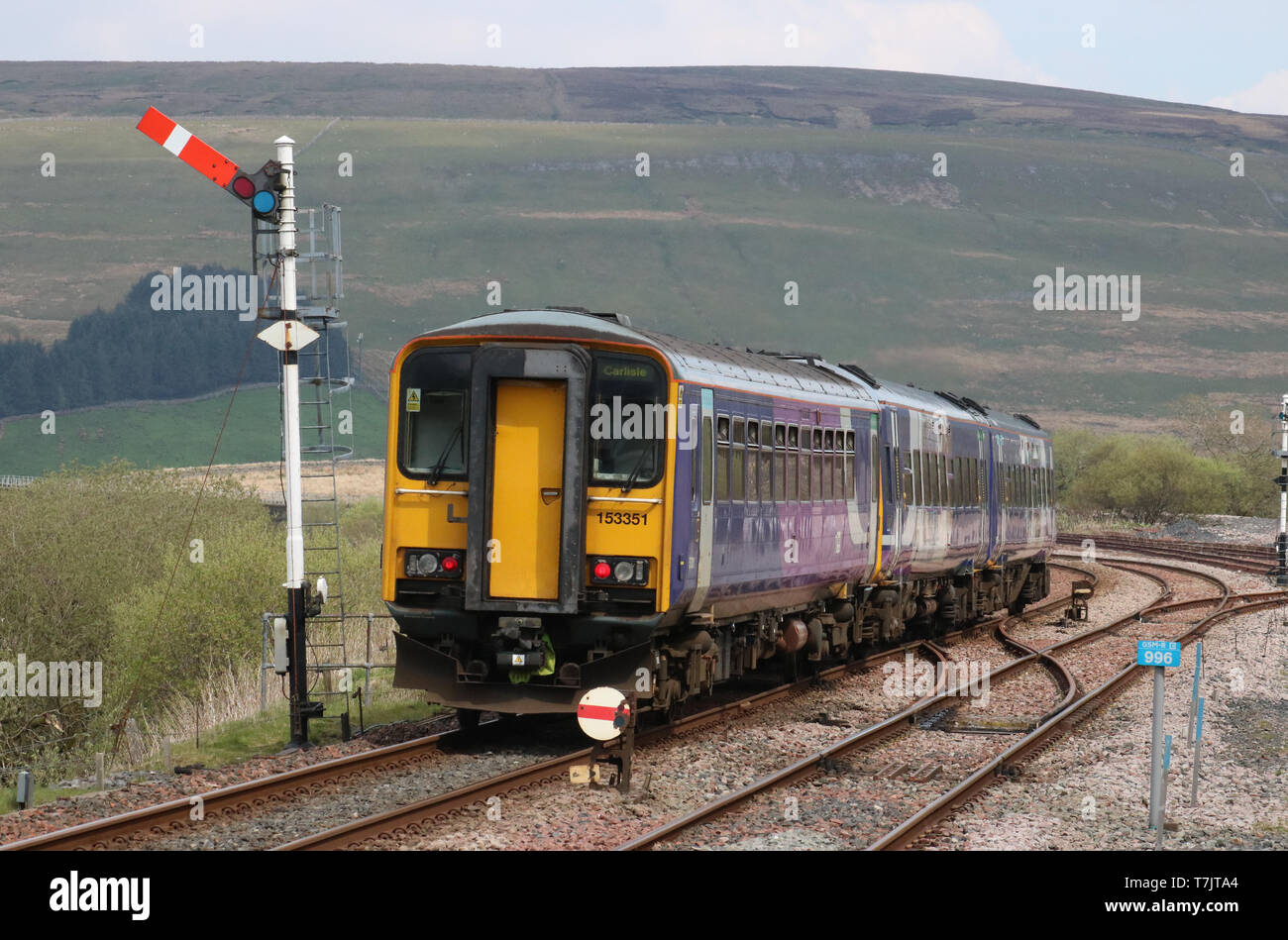 Northern train leaving at Garsdale station on the Settle to Carlisle railway line passing semaphore signal on 30th April 2019. Stock Photo