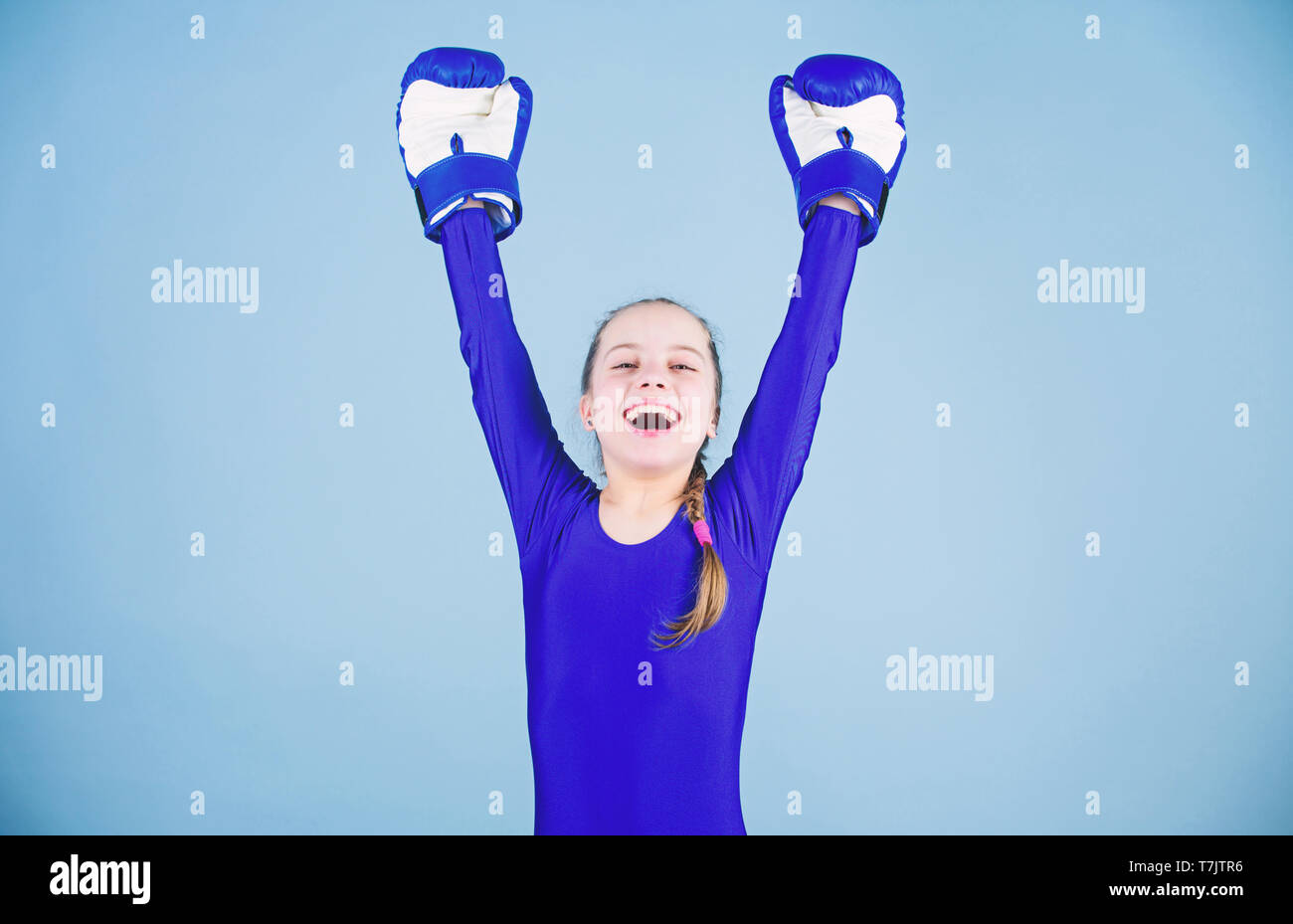 Risk of injury. Female boxer change attitudes within sport. Rise of women boxers. Girl cute boxer on blue background. With great power comes great responsibility. Boxer child in boxing gloves. - Stock Image