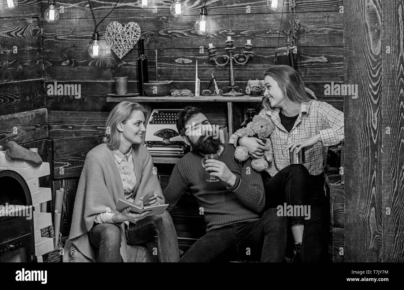 Girl holding teddy enjoys evening with parents. Bearded man sitting between his wife and child in countryside house. Beautiful mom and daughter looking at each other and smiling, family fun concept. Stock Photo