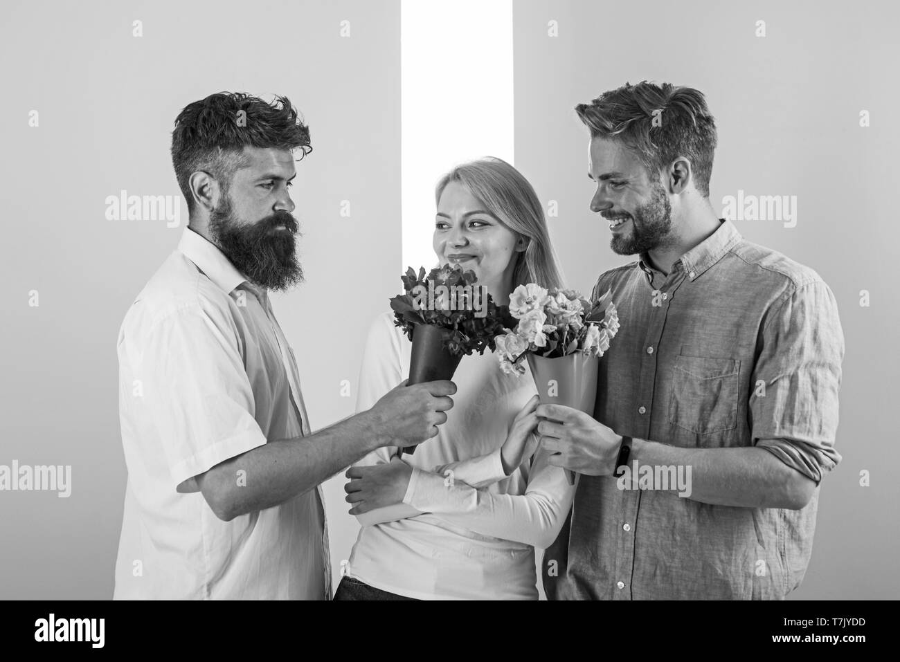 Girl popular receive lot men attention. Men competitors with bouquets flowers try conquer girl. Love triangle. Woman smiling has opportunity choose partner. Girl happy likes to be in middle attention. - Stock Image