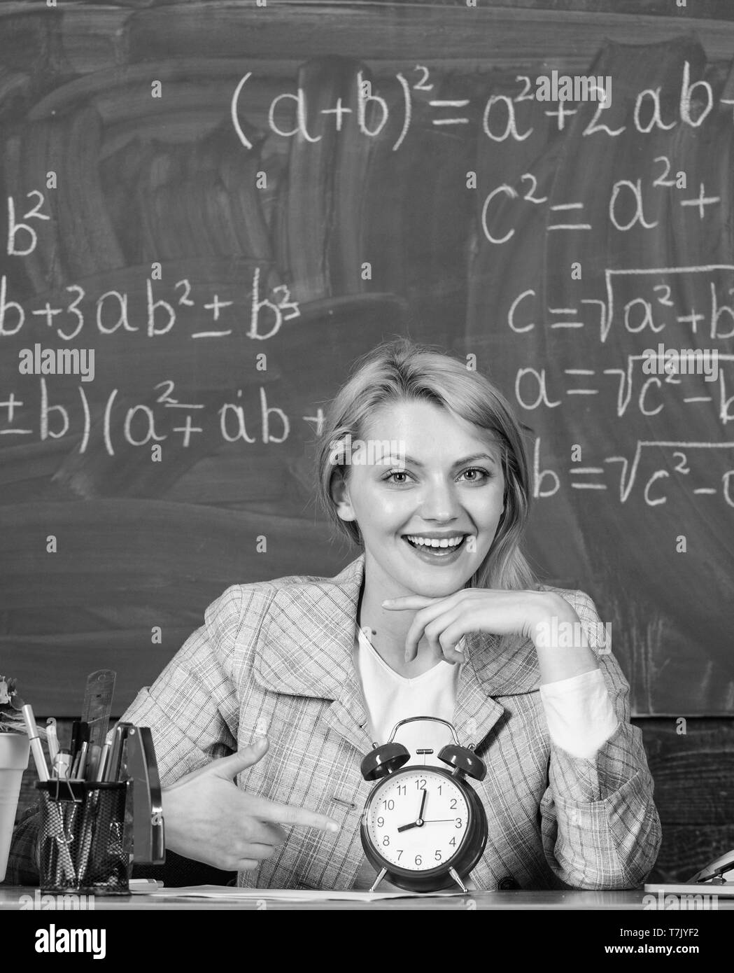 Confidence and punctuality. Study and education. Modern school. Knowledge day. Back to school. Teachers day. School. Home schooling. happy woman. woman in classroom. teacher with alarm clock. Time - Stock Image