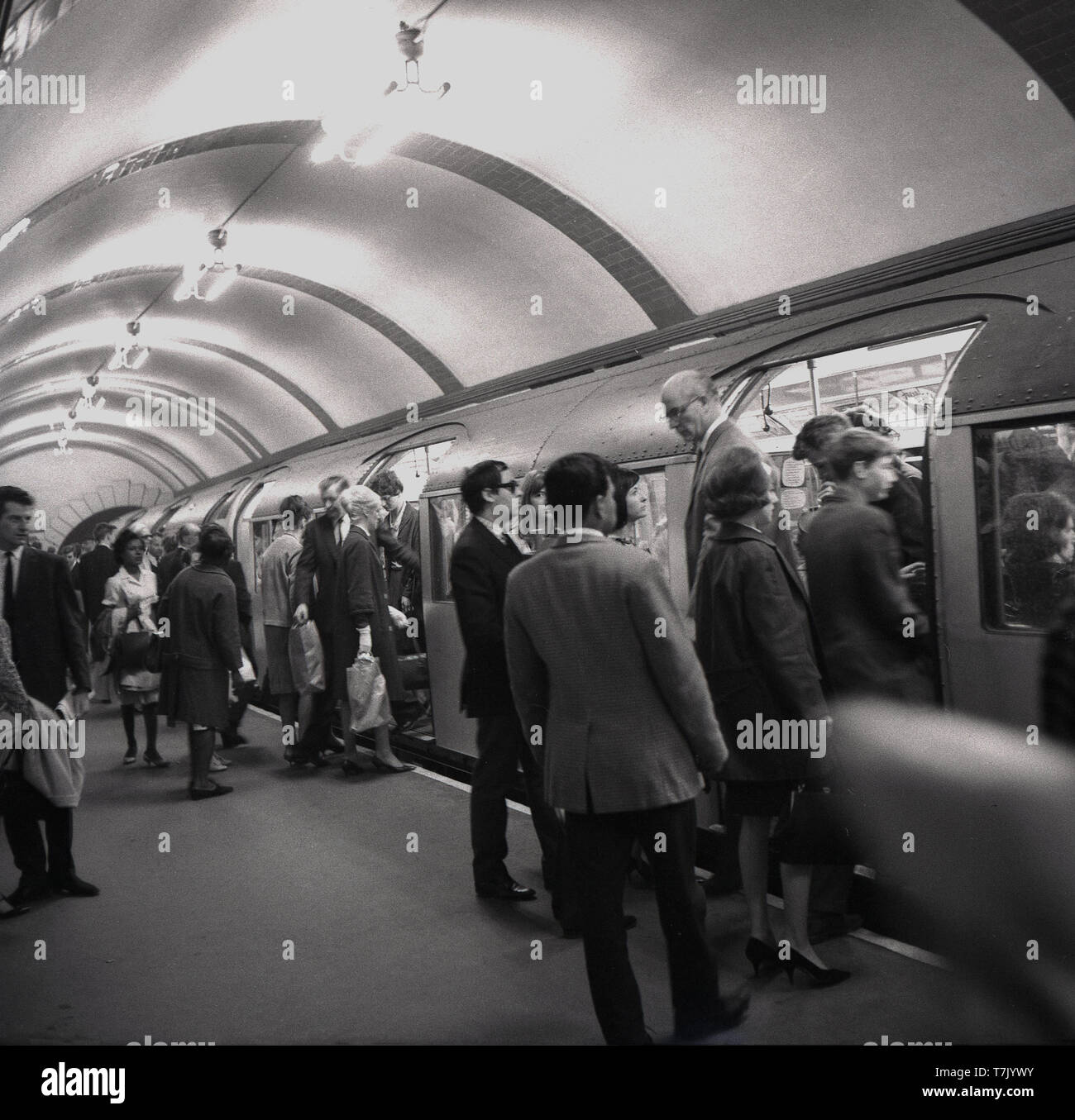 1960s, historical, London Underground, a tube train at a platform, people getting on and off the train, London, England, UK. The orgins of the London Underground lie in the Metropolitan Railway, the world's first underground passenger railway opened in 1863. Gas-lit wooden carriages were hauled by steam locomotives, - Stock Image