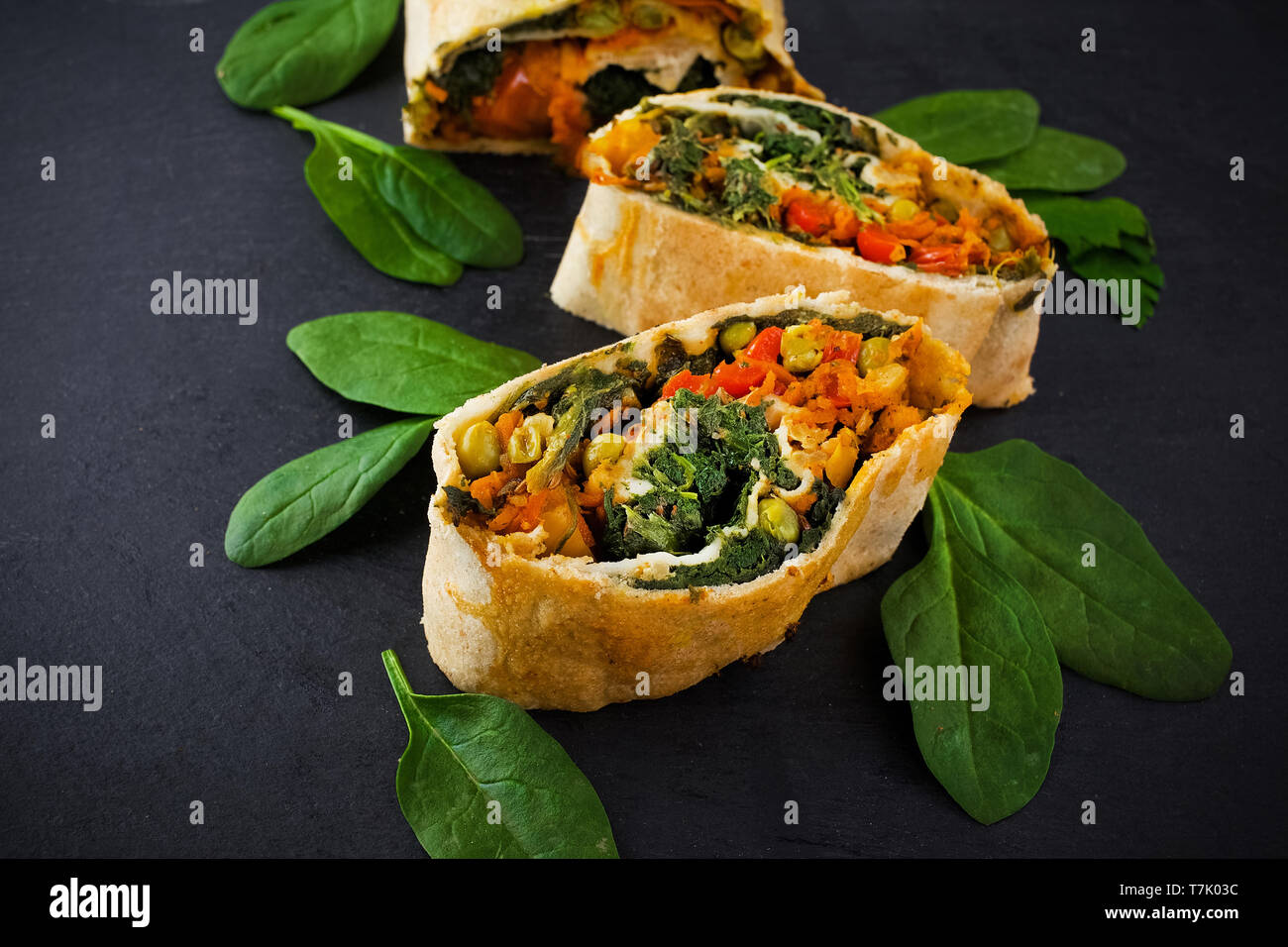 Vegetable savory strudel, with tomatoes and mushrooms on black background Stock Photo
