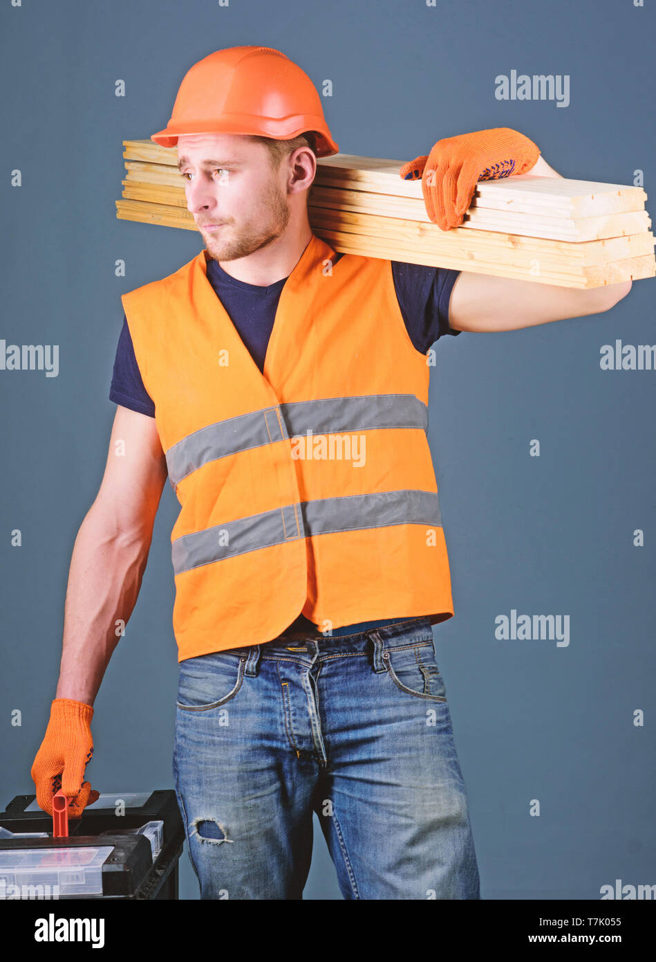 Woodcraft concept. Carpenter, woodworker, labourer, builder on busy face carries wooden beams on shoulder. Man, handyman in helmet, hard hat holds toolbox and wooden beams, grey background. Stock Photo