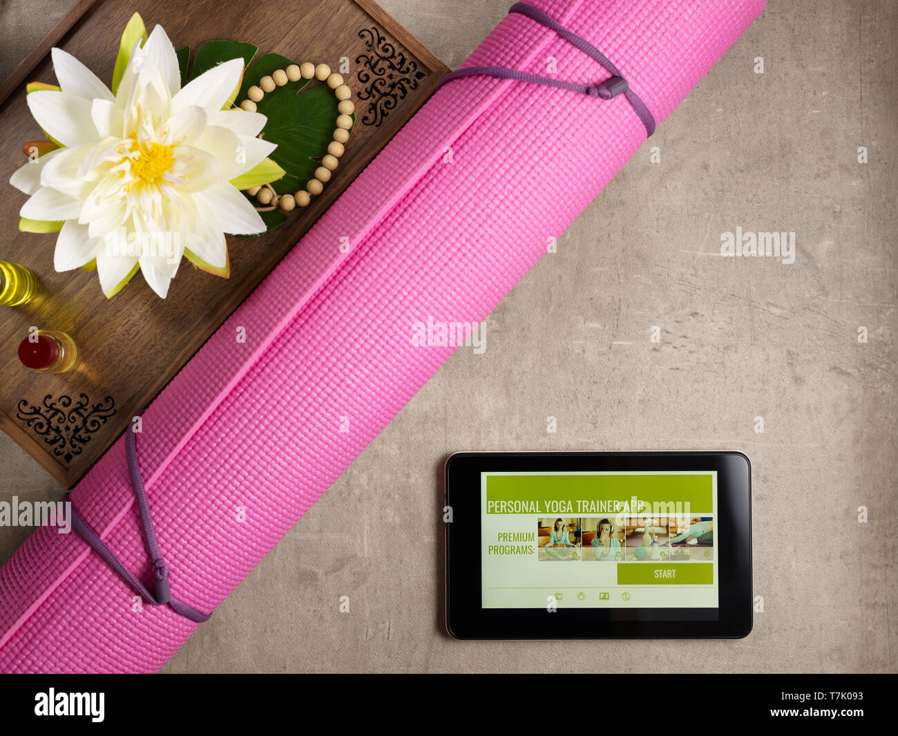 Closeup on tray with fragrant stuff for aroma yoga, beads, yoga mat and tablet PC with personal yoga trainer app laying on the floor. - Stock Image