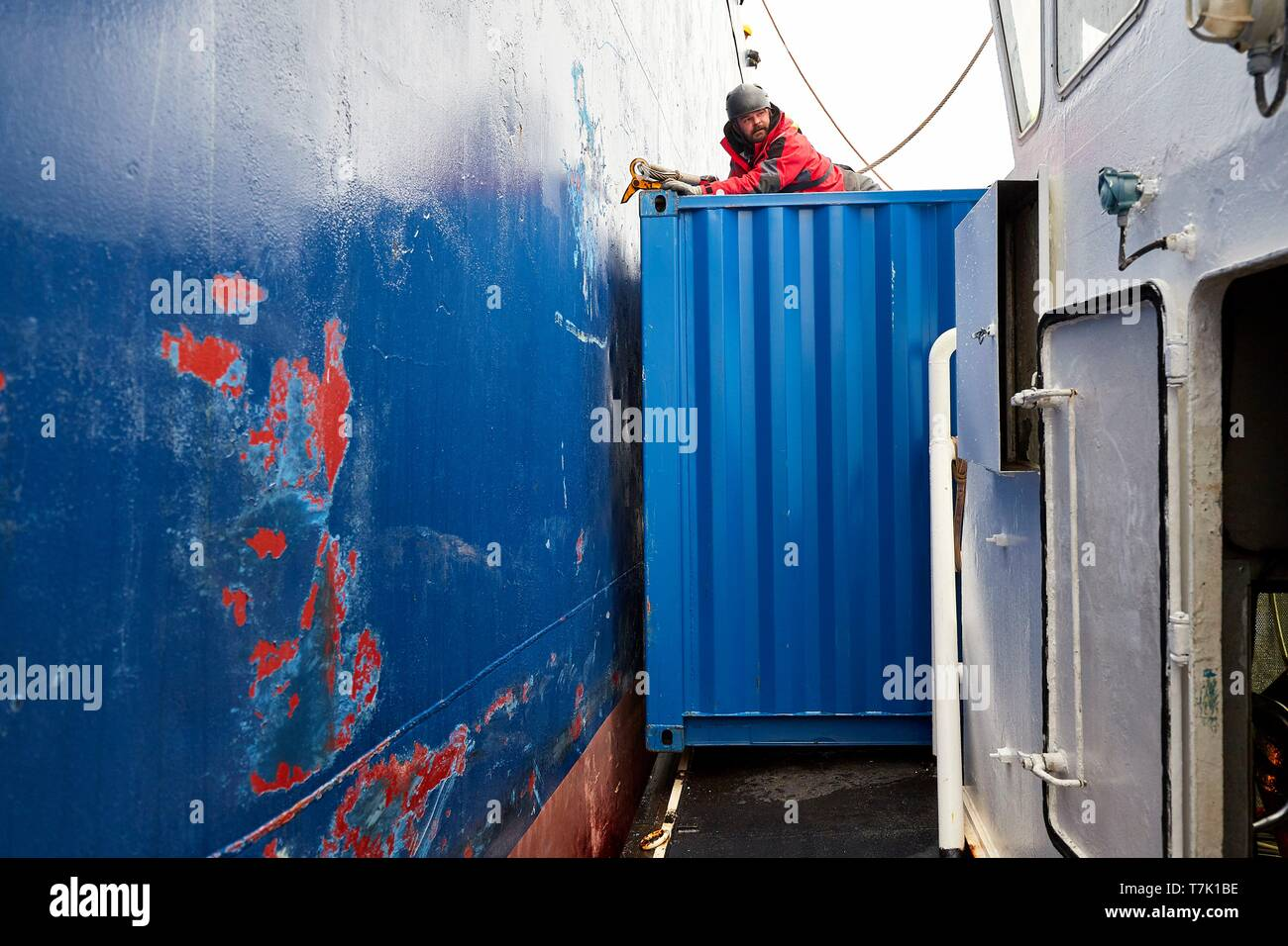 France, French Southern and Antarctic Territories (TAAF), Kerguelen Islands, Port-aux-Français, on board the barge Aventure II, the only boat of the island, which transports the heavy freight (container) between the Marion Dufresne and the pier of Port-aux-Français. A seaman sitting on a container during the approach of the Marion Dufresne - Stock Image