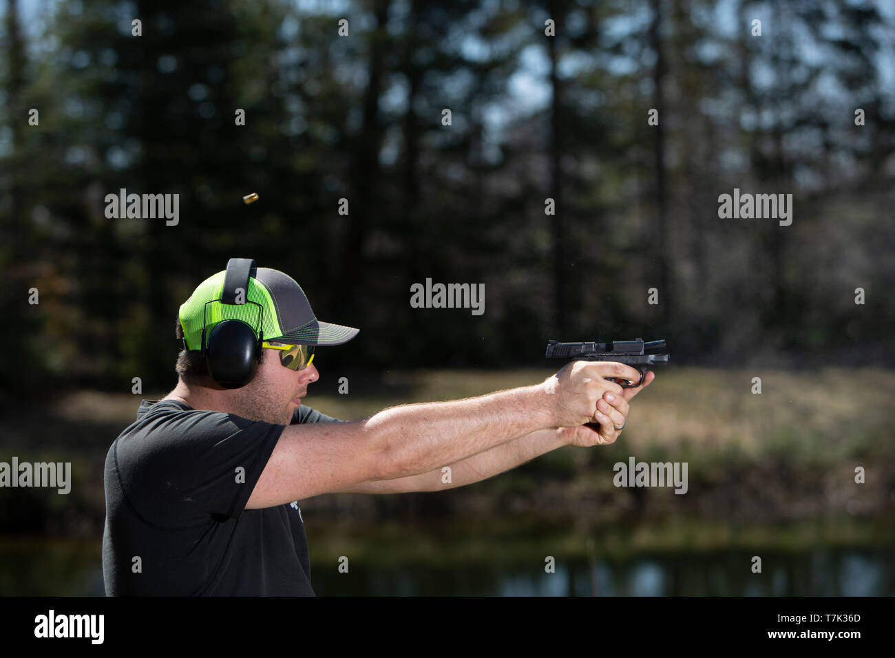 A man shooting a handgun with the ejected shell in the air. - Stock Image