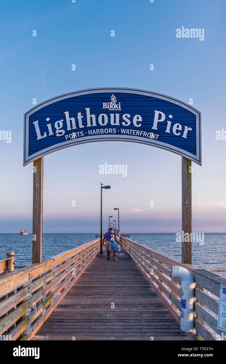 A Couple Walks Out On Lighthouse Pier At Dusk In Biloxi