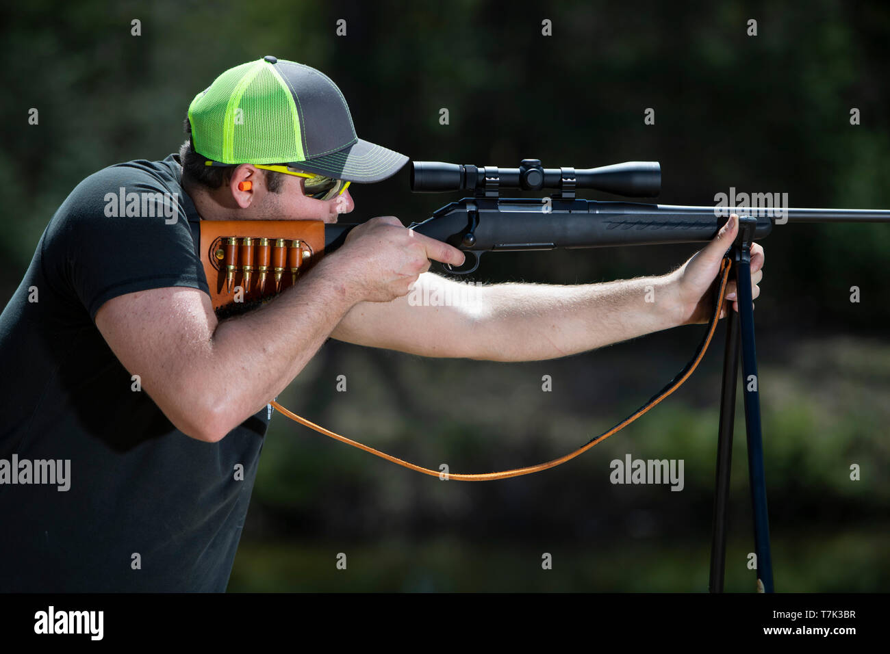 A man aiming a rifle that is resting on shooting sticks. - Stock Image