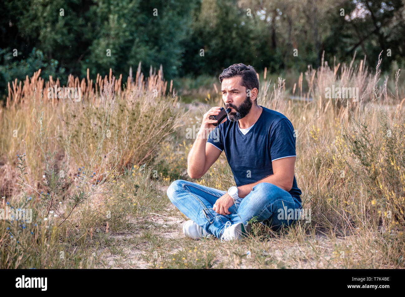 Stylish bearded vape man smokes e-cigarette exhales smoke on the ground. Electronic cigarette as alternative to tobacco. - Stock Image
