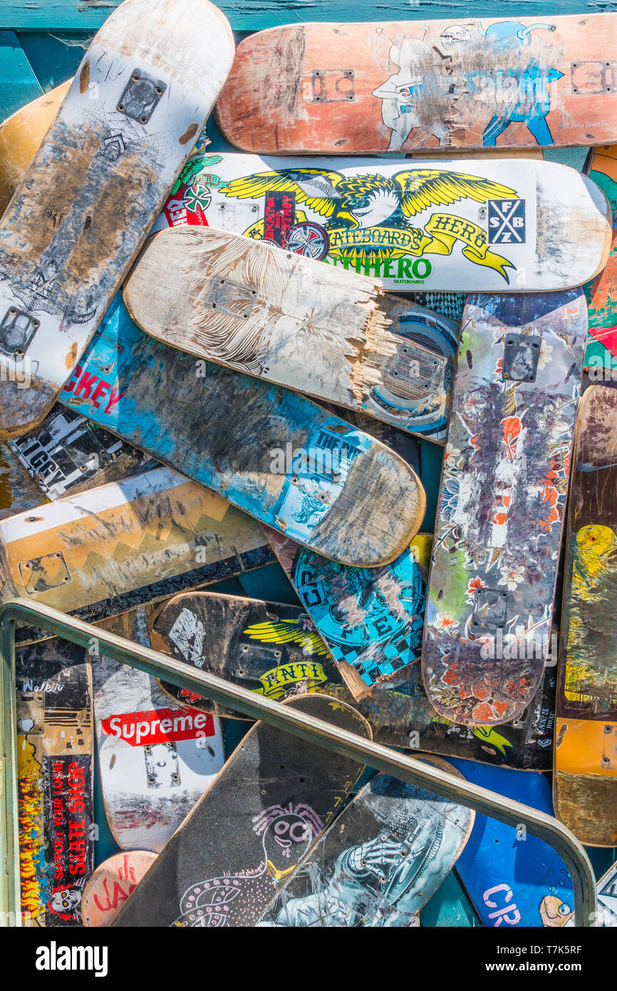 A pile of preowned skateboard decks arranged in a random fashion, some broken and some whole with each having a different design pattern in front of a - Stock Image