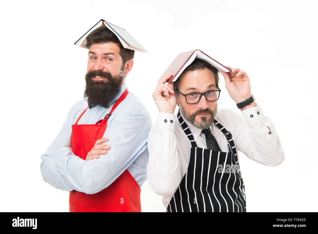 Men bearded apron reading book about culinary. Men in charge household. Some problems. Household duties. Book as roof on head. Household is boring. Who rules in house. Responsibilities of household. - Stock Image